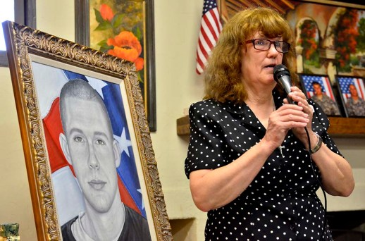 Club President Anita Bales stands in front of painting of fallen soldier Brandon Meyer.