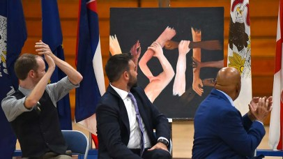 """Rep. John Lewis (right) and fellow """"March"""" authors turn to examine (and applaud) the """"Vote"""" painting by Morse High School students."""