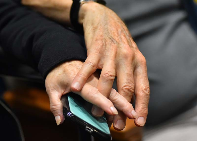 A couple held hands, and smart phone, at the community vigil at Congregation Beth Israel.