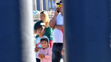 A family from Honduras stands on the Mexico side of the border.