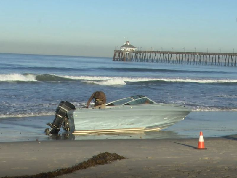 Border Patrol agents inspect boat on beach