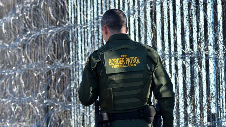 A Border Patrol agent walks along he newly installed concertina wire at Border Field State Park.