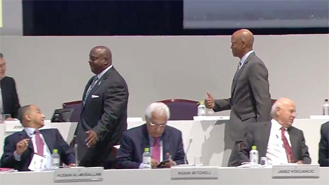 Trailing Vincent Mudd, Willie Banks gives a thumbs up to members on the dais at the ANOC General Assembly.