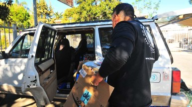 Hugo Castro, who heads the migrant efforts in Tijuana, packs a vehicle with donated items for migrants.