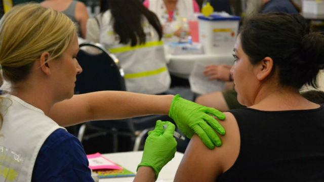 A woman receives a flu shot