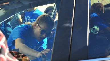 Border Angels volunteer Cynthia Hunter reaches in her car for donations as people crowd around the car.