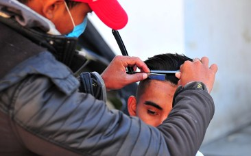 A young migrant gets a haircut from a barber stationed at the end of the family tent area.