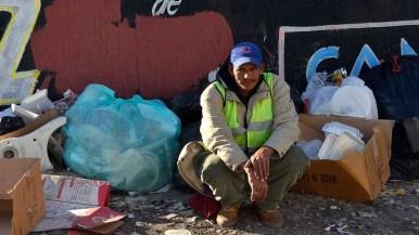 A man sits outside El Barretal among the trash.
