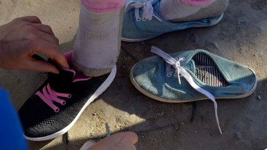 Border Angel volunteer Cynthia Hunter tries a new pair of shoes on a young girl. Many migrants wore flip-flops or shower shoes.
