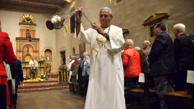 Deacon Andy Orosco of San Bernadino swings the incense censer down the aisle of the mission during the prayer service.