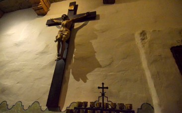 A crucifix hangs from the mission wall near candles in the back of the church.