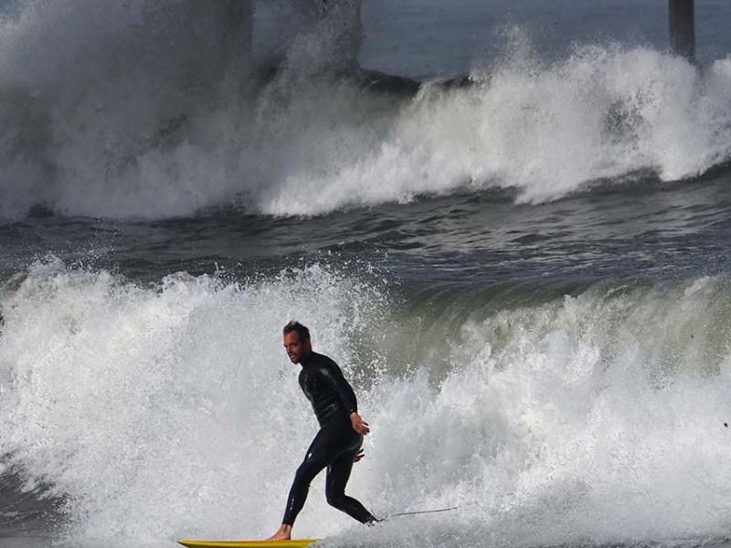 A surfer enjoys the king tides at high tide at Ocean Beach Pier.