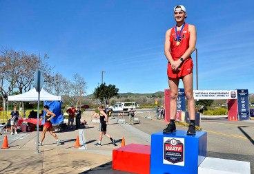 High school senior Logan Roberts Jr. wears his 10K gold medal as 50K racers pass behind him.