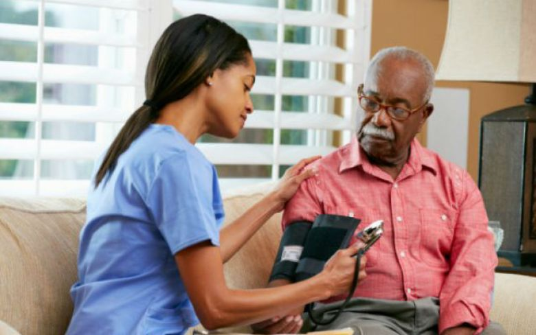 A home health care worker checks a man's blood pressure