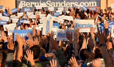 Members of the crowd raise their hands in support of Bernie Sander's policy ideas and his presidential candidacy.