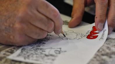 Legendary MAD Magazine artist Sergio Aragonés draws an Alfred E. Neuman drawing for a comic fest attendee.
