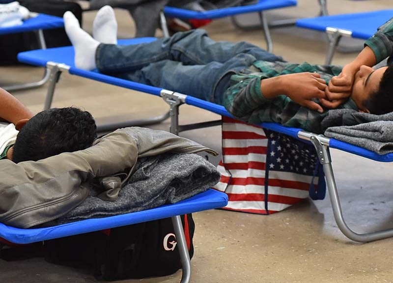 Two young men seeking asylum rest on cots while waiting to begin their journey to their sponsors.