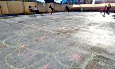 Children's chalk drawings brighten an outdoor area where children can play while awaiting their time to travel further.
