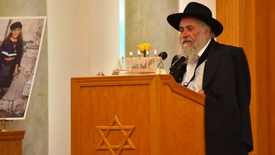 Rabbi Yisroel Goldstein of Chabad of Poway holds a yellow rose to symbolize Lori Kaye's generosity.
