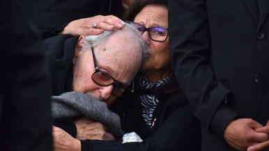 Richard S. Gilbert, father of Lori Kaye, is comforted at the grave of his daughter at El Camino Memorial Cemetery.