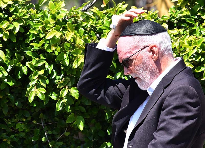 A man with a bandage and a blood spot on his hand was seen walking away from the synagogue in Poway.