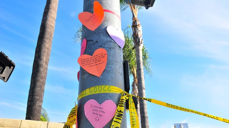 A neighborhood family taped hearts with supportive messages on a street light post across from Chabad of Poway.