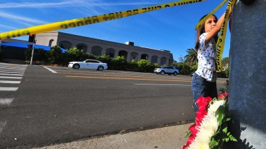 A young girl attaches hearts to a light pole across the street from Chabad of Poway.