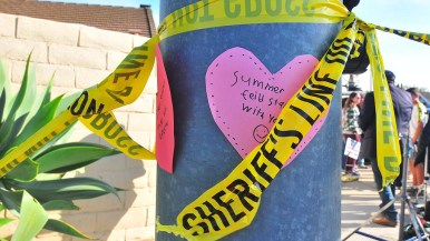 A mother and two children put up hearts on a a light pole across the street from Chabad of Poway.