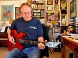 Max Branscomb plays guitar in the study of his Bonita home.