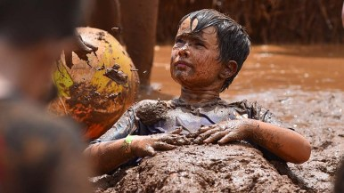 Isaiah Sybor, 7, of Clairemont enjoys a mud bath in the mud pit at Crown Point on International Mud Day.