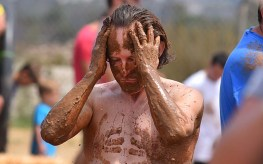 Curtis B. of San Diego applies mud in a mud pit at Crown Point on International Mud Day.