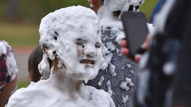 A young girl, covered with soapy foam, poses for a cellphone photo at the International Mud Day activities at Crown Point.