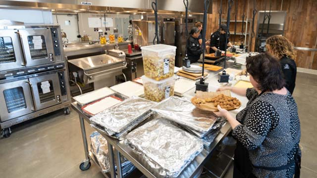 Employees prepare meals for the food insecure at the Green Oceanside Kitchen, a facility that opened in June 2019.