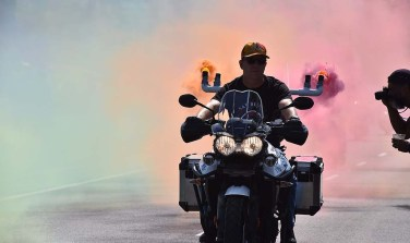 A member of the motorcycle contingent spreads colorful smoke at the beginning of the 2019 San Diego Pride Parade.