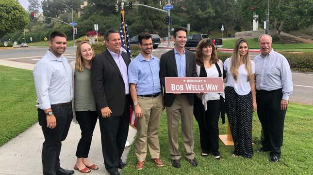 Councilman Mark Kersey holds sign of Bob Wells Way in Rancho Bernardo.