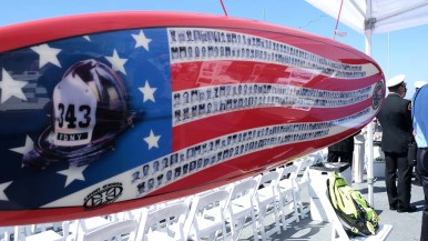 A surfboard with photos of the 343 firemen who died on Sept. 11, 2001 was on display at the Midway ceremony. Photo by Chris Stone