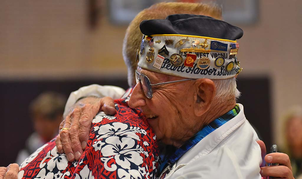 Pearl Harbor survivor Stu Hedley is hugged by honorary member Dwight Hanson at the meeting.