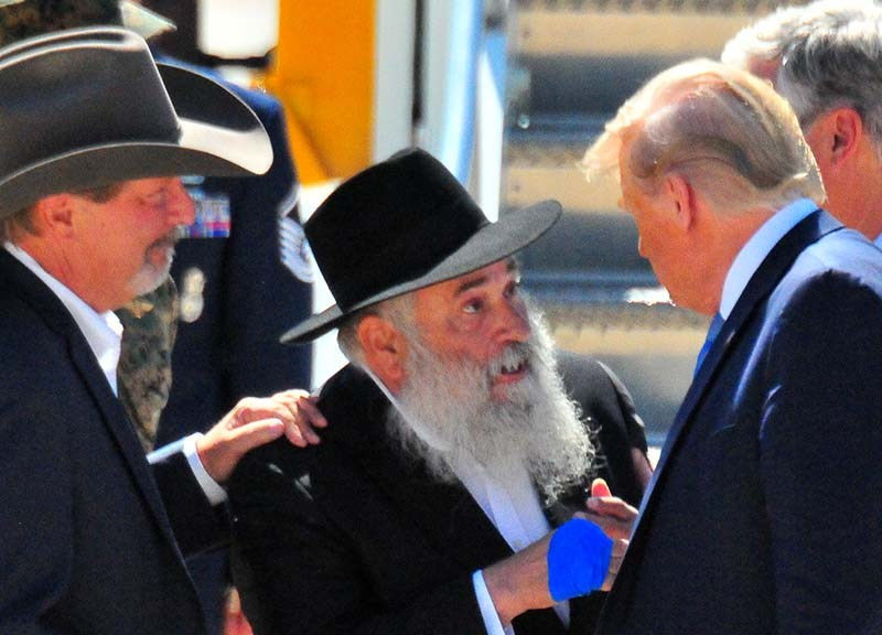 As Poway Mayor Steve Vaus looks on, Rabbi Yisroel Goldstein chats with President Trump.