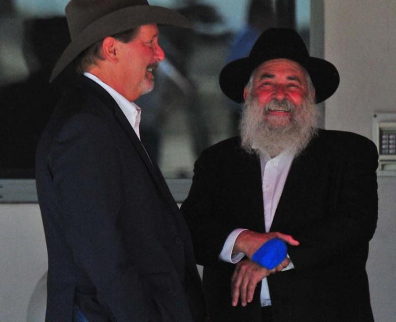 Rabbi Yisroel Goldstein and Poway Mayor Steve Vaus stay cool in shade before greeting President Trump.