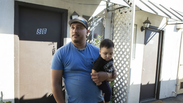 Alex Espinoza with his son outside the unit his family is being evicted from