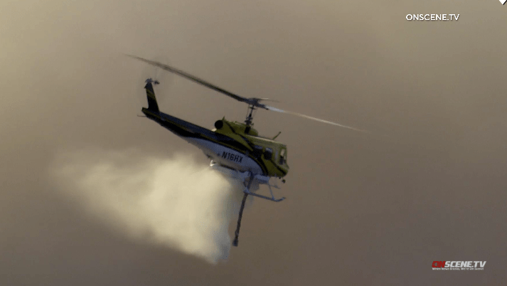 A helicopter drops water on Valley Center's Miller Fire.