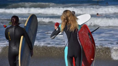 Two paddle out participants head to the sea to honor ocean scientist Walter Munk.