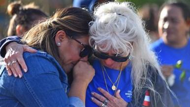 Munk friend Terry Kraszewski (right) comforts Maggie Velazquez, a former caregiver of Walter Munk during the ceremony.