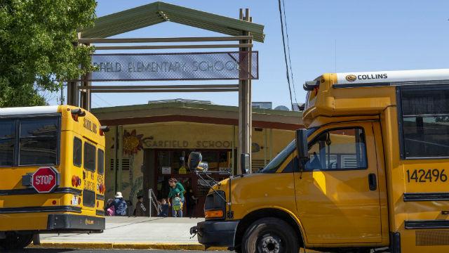 School buses line up outside of an elementary school in Oakland