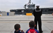 Boys wait for their father as the USS Abraham Lincoln is pushed to shore by tugs.