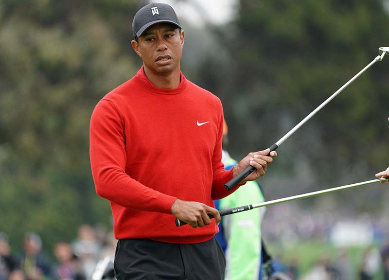 Tiger Woods hands off one club to his caddie as he grabs another.