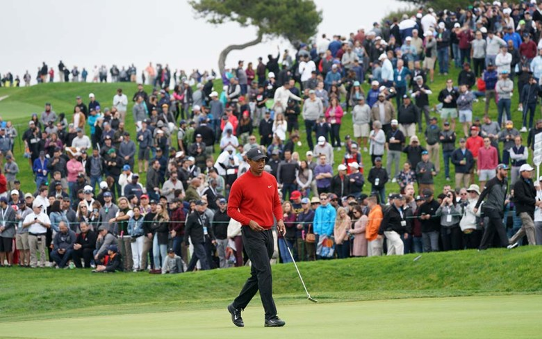 Fans watch Tiger Woods putt on the 5th green of the south course of the Farmers Insurance Open in the fourth round.