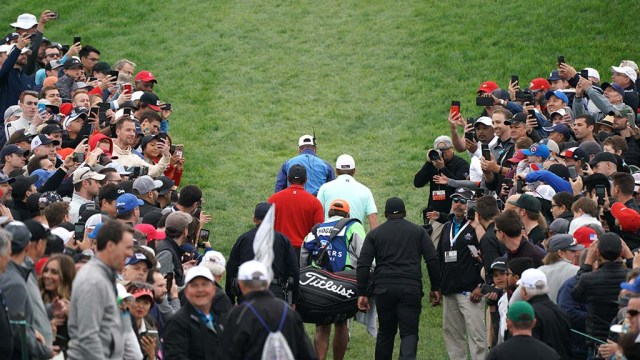 Tiger Woods and Tom Hoge leave the 5th green as fans crane to get a photo.