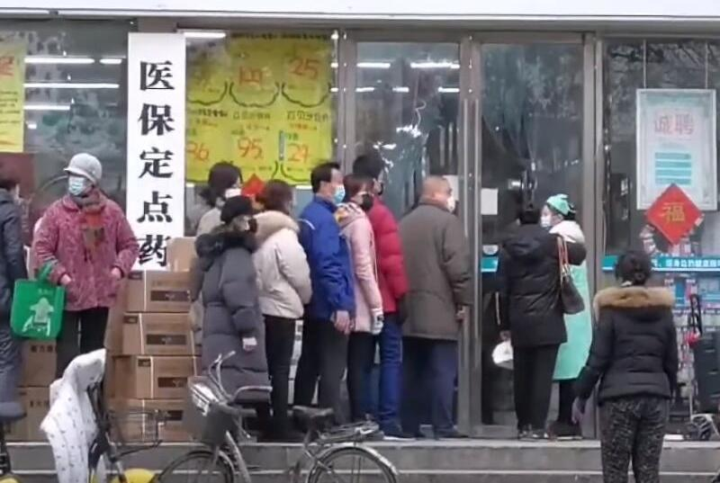 Residents of Wuhan line up at a pharmacy