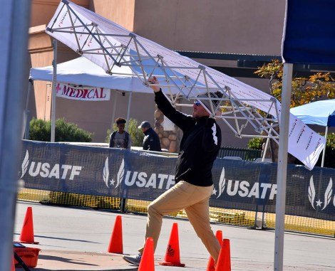 Promoter Dan Cruz of San Diego moves USATF-branded backstop at Olympic Trials 50K walk.
